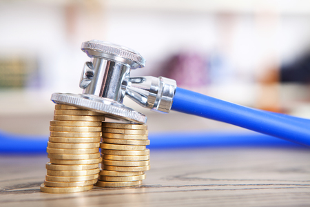 The coins under the stethoscope Stock Photo