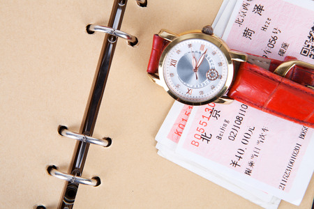Train tickets on a brown notebook page with a watch Editorial