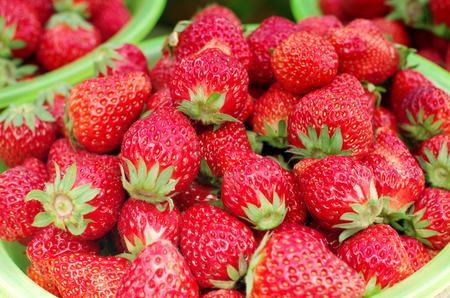 Fresh strawberry in a plastic container close up view