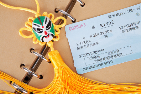 Train tickets on a brown notebook page with a Chinese traditional knot Editorial