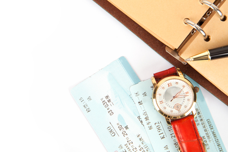 Notebook and a watch with train tickets on white background