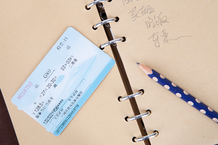 Train tickets on a brown notebook page with a pencil Editorial