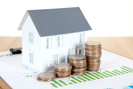 Small house model and dollar coins Stock Photo