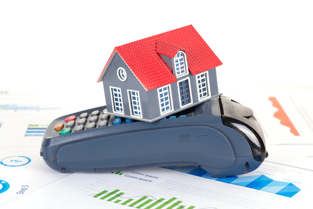 House model and pos machine on financial chart Stock Photo