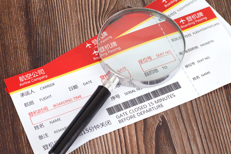 Air ticket and magnifying glass