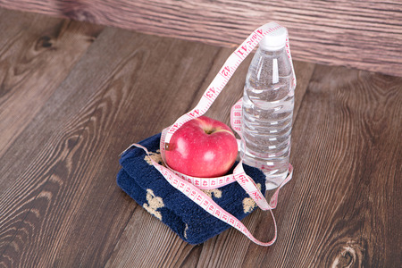 a bottle of water and a ruler apple and towel
