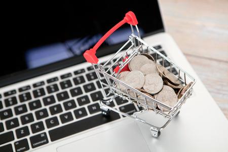 Trolley model full of dollar coins on laptop