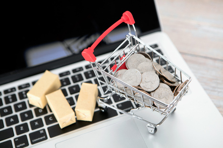 Laptop model and cargo loaded with dollar coins on laptop Imagens