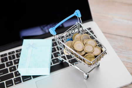 Trolley model and gift loaded with euro coins on laptop