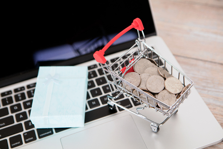 Trolley model and gift loaded with dollar coins on laptop
