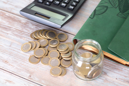 Piggy bank and calculator and euro coins on the table Imagens