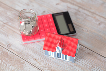 Saving money glass jar on calculator and model house next to it
