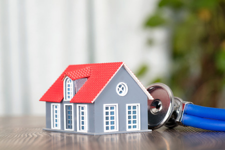 Small house model and stethoscope Stock Photo
