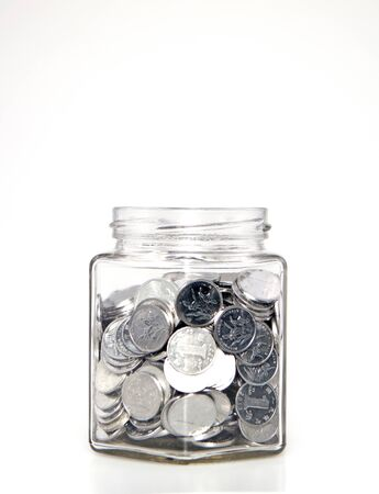 Glass jar filled with coins Banco de Imagens