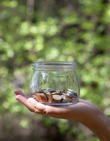 Hand holding a money glass jar Imagens