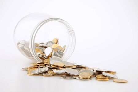 Glass jar and scattered coins