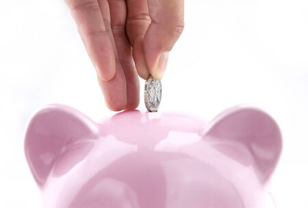 Saving money into piggy bank Imagens