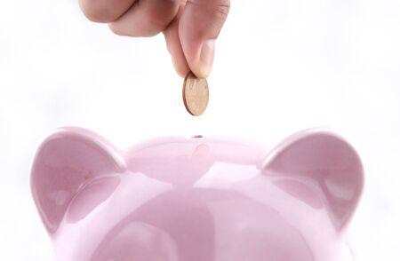 Savings concept, save coins into piggy bank Imagens