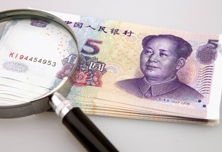 Five yuan currency and magnifying glass