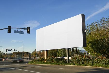 Publicidad en cartelera en una avenida con un fondo de cielo azul Foto de archivo