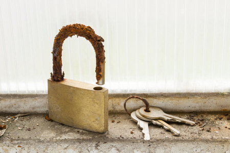 Someone forgot to padlock and its corresponding set of keys at the bottom of a window. Stock Photo