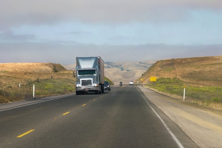 A cargo truck and other vehicles circulate on a road in a rural area of ??the state of California in the United States.