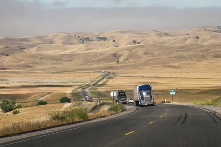 Freight trucks circulate by road passing between mountains of a rural area of ??the state of California in the United States.