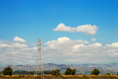 Electric power tower framed by a beautiful rural landscape with blue sky and white clouds. Stock Photo
