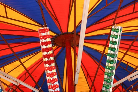 Detalle de un juego mecánico donde el efecto de retroiluminación resalta los colores de la tienda que forma parte de su estructura. Foto de archivo