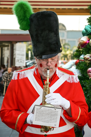 LOS ANGELES, CALIFORNIA, USA, DECEMBER 23, 2006 - A man in a suit that reminds us of the tale of the lead soldier plays carols on his saxophone during the christmas season at The Grove mall.
