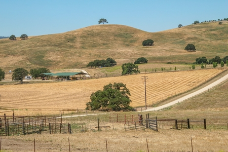 CALIFORNIA, USA - JUNE 10, 2006. Panoramic view of a plowed farm field within a ranch at the foot of some hills in the so-called Golden State, California, United States.