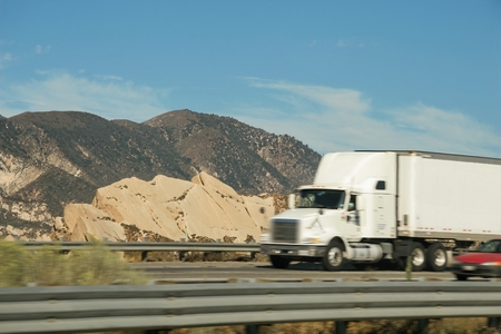 Lateral view of a tow truck driving along with other vehicle on Interstate Freeway No. 5 in the vicinity of the areas of Gorman, Lebec and Gravepine in the state of California in the United States.