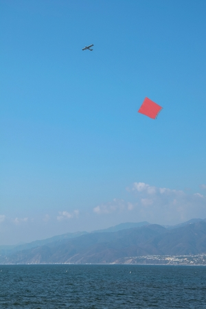 An empty canvas in red used for advertisements is pulled by a plane that flies over the sea from Santa Monica Beach, California in the United States.