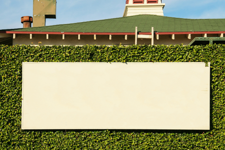 Front view of an empty rectangular panel ready to be announced on it, placed on an ivy-covered wall in the city of Los Angeles, California in the United States. 版權商用圖片