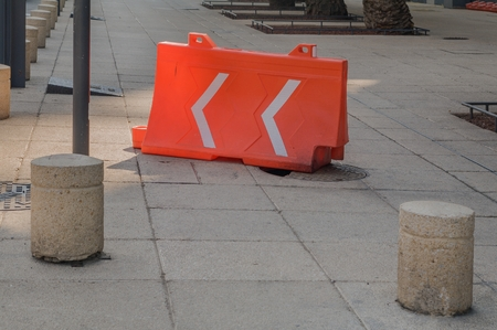 Take in horizontal format of a broken culvert covered with an orange plastic structure of those used in construction work to create safety barriers and control the traffic of vehicles and people. Republic Square, Mexico City.