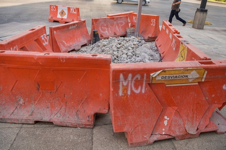 Take in horizontal format of some orange plastic structures used as security barriers and control traffic of vehicles and people during the construction works of Metrobus Line 7 on Reforma Avenue in Mexico City.