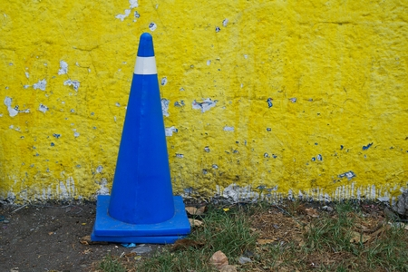 Take in horizontal format of a cone of vehicular control of plastic in royal blue color on a land with grass and a yellow and peeling wall in Mexico City. 版權商用圖片