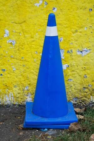 Take in vertical format of a cone of vehicular control of plastic in royal blue color on a land with grass and a yellow and peeling wall in Mexico City.