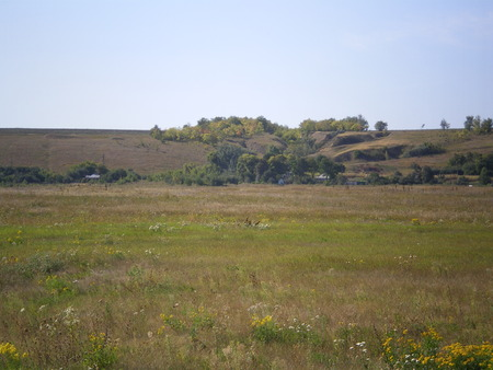 a meadow with green grass. a hill and a ravine covered with wood and rural houses in the distance. beginning of autumn