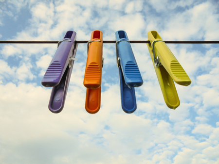 four multicolored plastic clothespins of yellow purple orange blue hanging on a rope against a blue sky