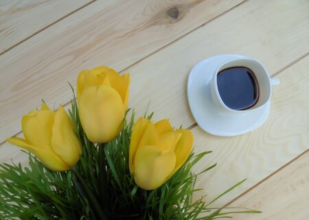 three beautiful yellow tulips and green grass a white cup with a saucer with coffee on wooden boards