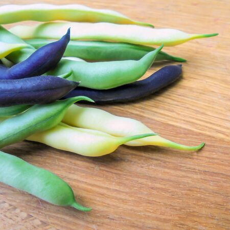pods of young asparagus bean yellow purple and green color lie on a wooden board