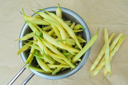 young yellow string beans are collected in a metal ladle and a few pods lie side by side on paper Stock Photo