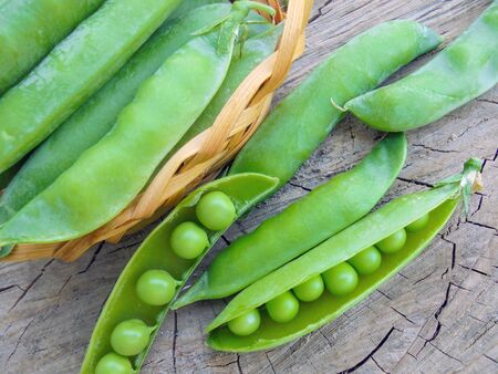 young green peas in green pods lie in a basket on a wooden surface