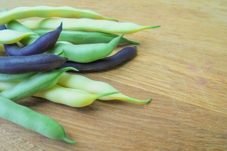 A variety of varieties of young green asparagus beans of green yellow and purple colors lie on a wooden surface