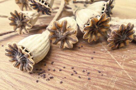 Semillas secas de semillas de amapola y semillas de amapola, algunas fuera de foco yacen sobre una superficie de madera