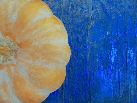 delicious orange ribbed pumpkin half visible on blue wooden background top view copypace Stock Photo