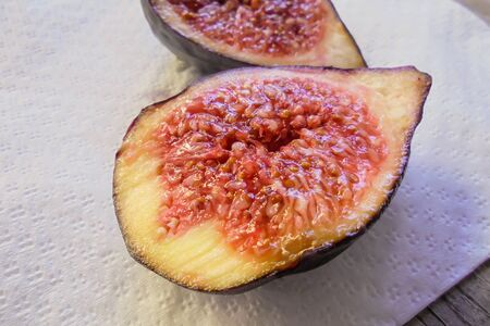 delicious juicy fruit of fresh purple figs cut in half lying on a white napkin on the table