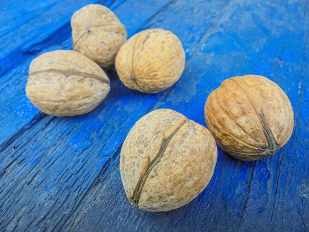 Five ripe dry tasty whole walnuts lie on a blue wooden background. Selective focus on two nuts. the rest of the nuts in the defocus Stock Photo