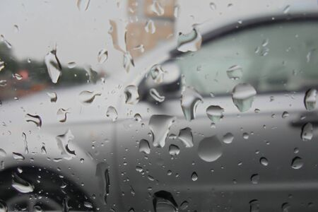 raindrops on a car glass view from a car interior. blurred background from a gray car Stockfoto